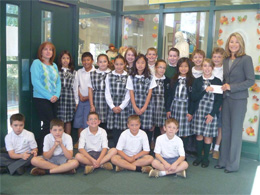 Laura McGill and her 5th grade class from St. Stephen present the check for $900 to Miles of Hope ED Pari Forood